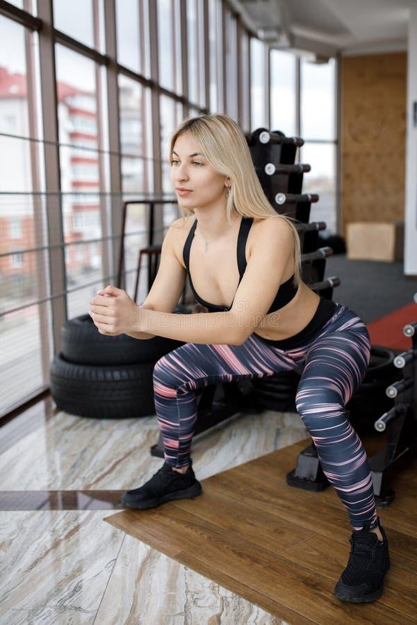 Belles jeunes position de sportive et postures accroupies de faire dans le gymnase Style de vie actif Sports dans le gymnase images stock
