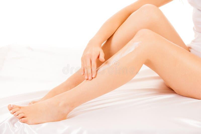 Belles longues jambes de femme mince et élégante d'isolement au-dessus du fond blanc image stock