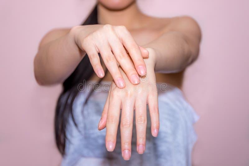 Belles mains de femme appliquant la crème photo stock