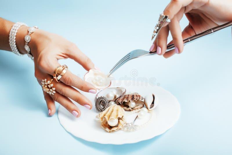 Belles mains de femme avec la manucure rose tenant le plat avec des perles et des coquilles de mer, concept de luxe de bijoux image stock