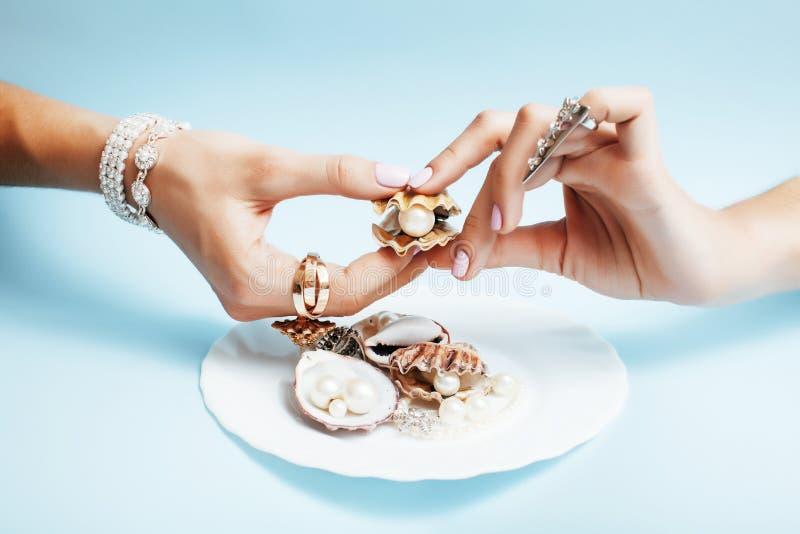 Belles mains de femme avec la manucure rose tenant le plat avec des perles et des coquilles de mer, concept de luxe de bijoux photographie stock