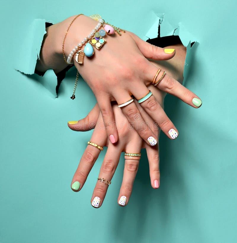 Belles mains de femme avec le vernis à ongles blanc rose jaune de modèle images stock