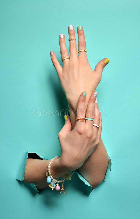 Belles mains de femme avec le vernis à ongles blanc rose jaune de modèle images libres de droits