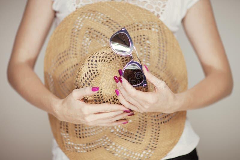 Belles mains de femme avec le vernis à ongles rose parfait tenant le chapeau de soleil et les lunettes de soleil, humeur heureuse images stock