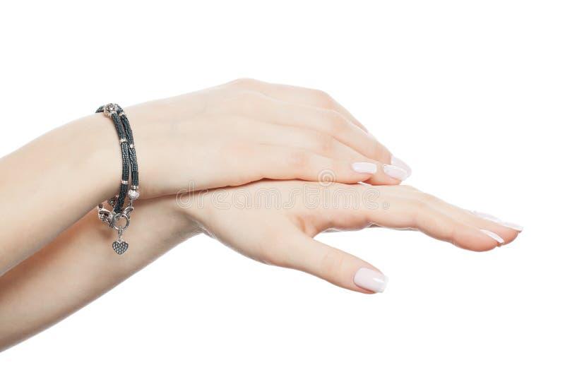Belles mains femelles avec le bracelet argenté de bijoux d'isolement au-dessus du fond blanc photographie stock libre de droits