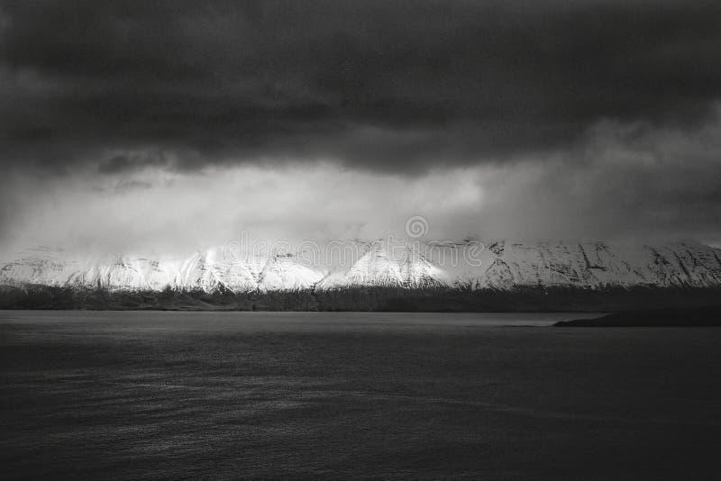 Belles montagnes neigeuses avec un lac et un ciel nuageux foncé photos stock