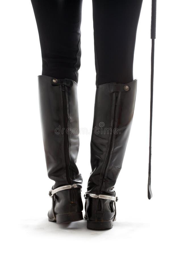 Belles pattes dans les gaines en cuir noires de cavalier avec la cravache photo stock