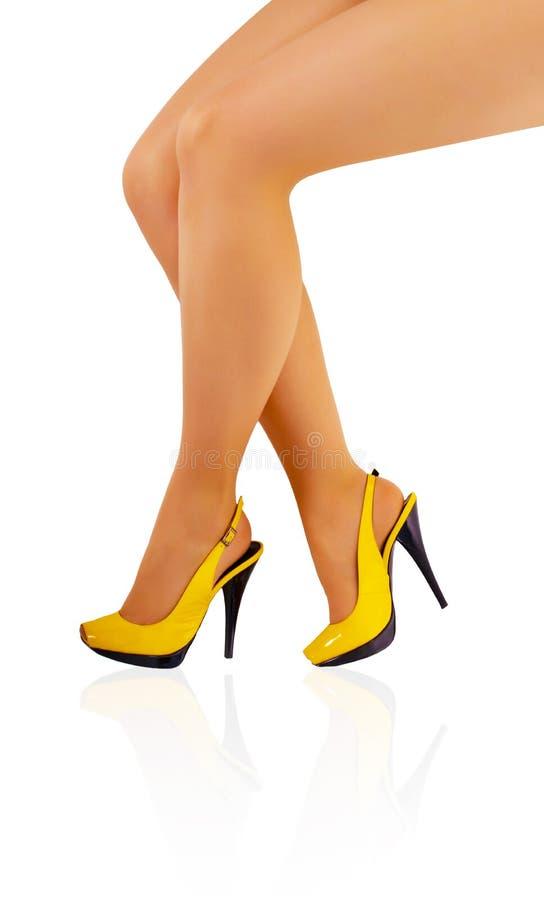 Belles pattes de jeune fille dans des chaussures jaunes photographie stock libre de droits
