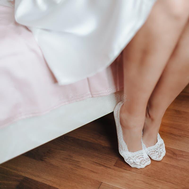 Belles pattes La cheville mignonne du ` s de jeune mariée se repose sur le lit images stock