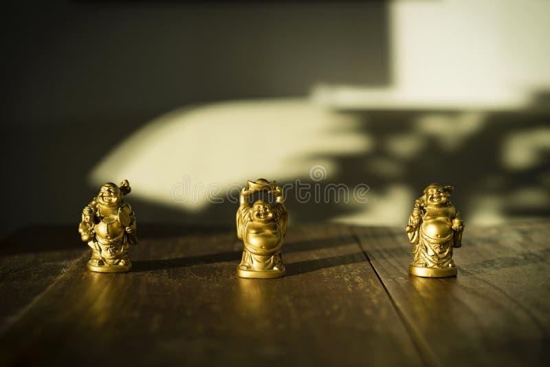 Belles petites statues d'or de Bouddha se tenant sur la table en bois foncée au soleil image stock