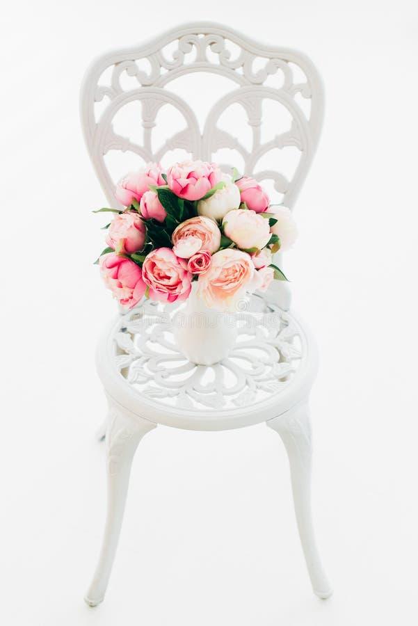 Belles pivoines de bouquet sur la chaise forgée de vintage dans la chambre blanche photos libres de droits