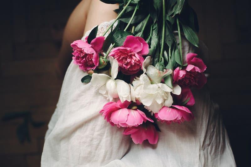 Belles pivoines roses sur des jambes de fille de boho dans la robe de Bohème blanche, vue supérieure L'espace pour le texte E photo libre de droits