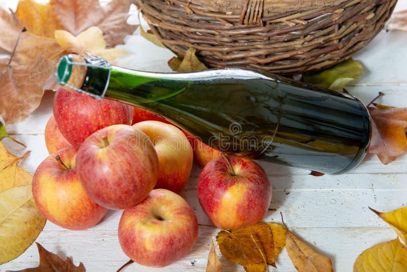 Belles pommes et bouteille de cidre, sur des feuilles d'automne image libre de droits