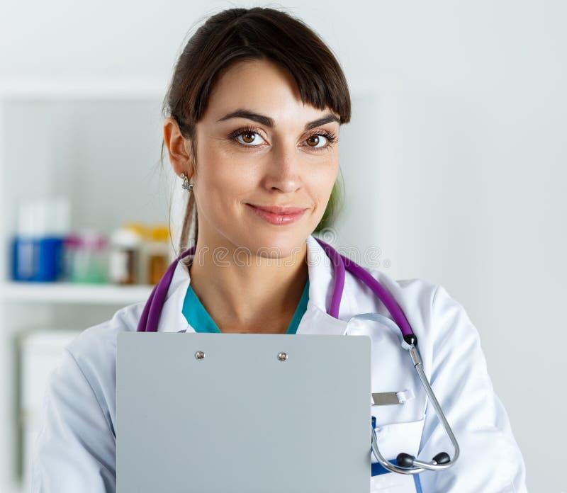 Belles prise de docteur et protection femelles de sourire de presse-papiers d'étreinte photos libres de droits