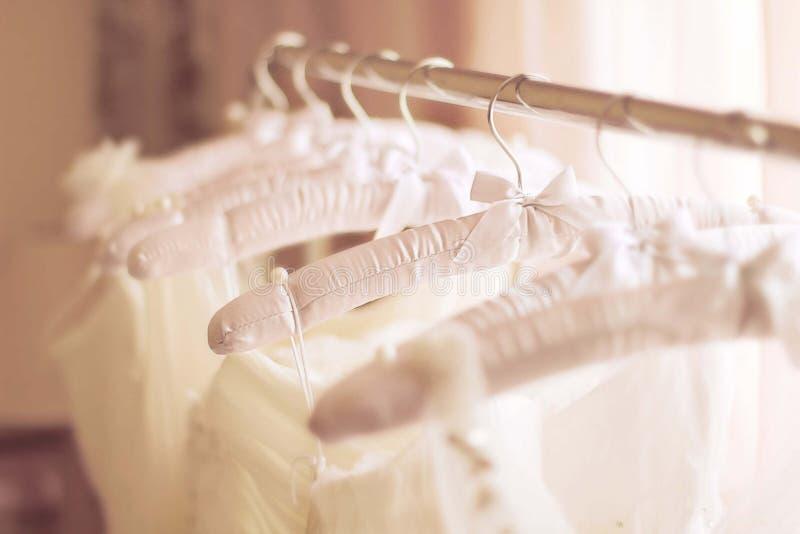Belles robes de mariage blanches faites de soie sur des cintres images libres de droits