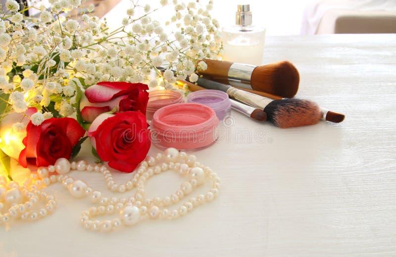 belles roses à côté de maquillage et parfum sur le fond en bois images libres de droits