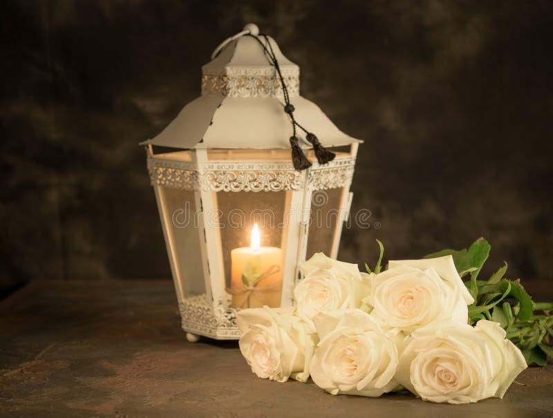 Belles roses blanches et bougie sur la table sur le fond noir photo libre de droits