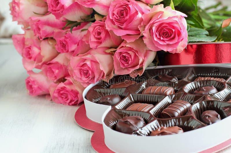 Belles roses roses molles avec une boîte de forme de coeur des bonbons au chocolat photos stock