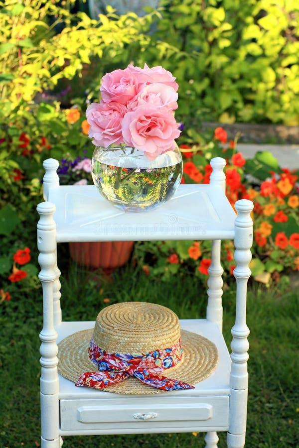 Belles roses roses dans un vase et un chapeau de paille photographie stock