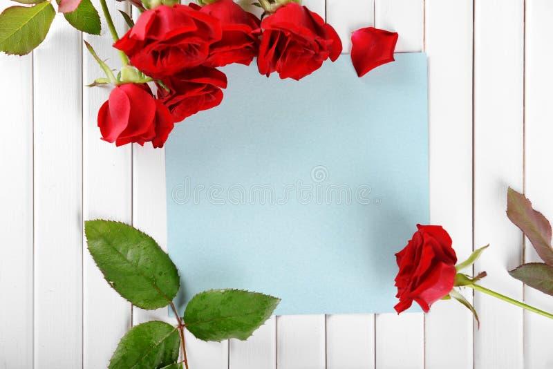 Belles roses rouges et carte vierge sur le fond en bois blanc images libres de droits