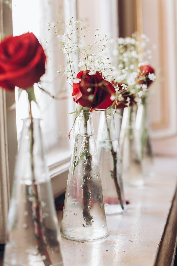 Belles roses rouges et souffle blanc de bébé dans des vases en verre sur le tabl images stock