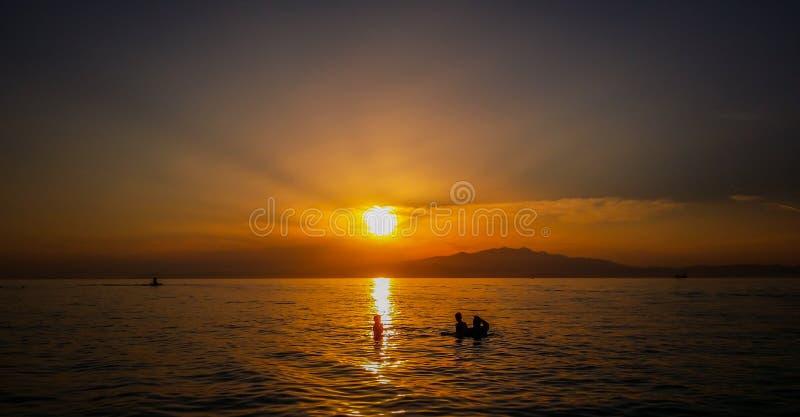 Belles silhouettes exotiques de lever de soleil et de peuples image stock