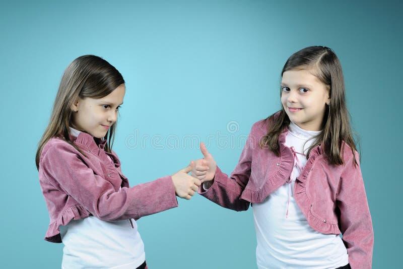 belles soeurs jumelles affichant le signe en bon état image stock