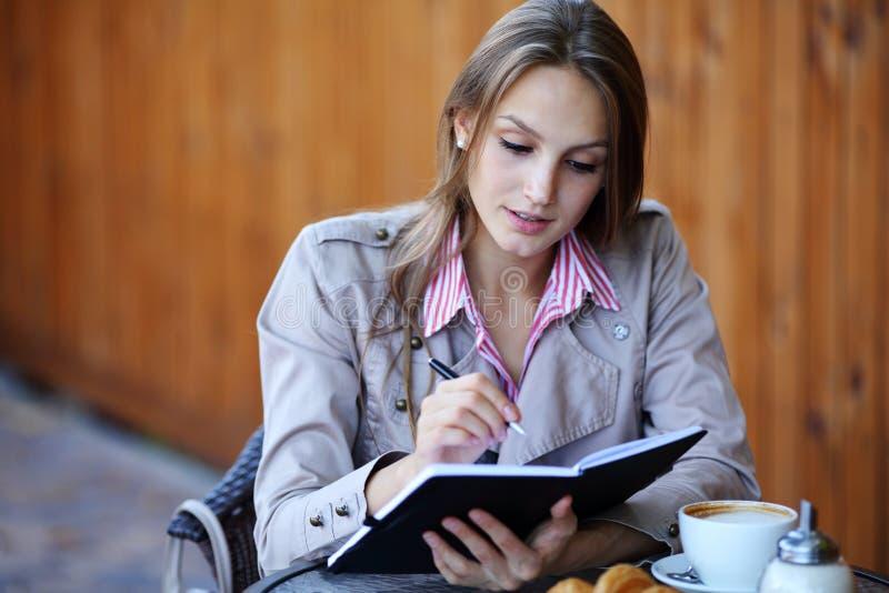 Belles tâches d'écriture de fille pendant un jour avec du café image stock