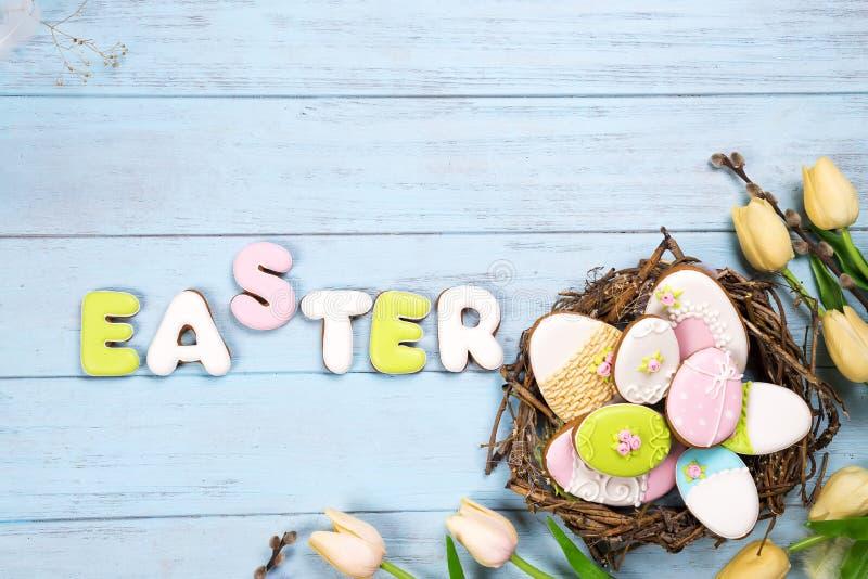 Belles tulipes d'e avec les oeufs colorés dans le nid sur le fond et les biscuits en bois bleus marquant avec des lettres Pâques images stock