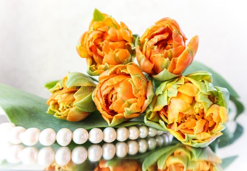 Belles tulipes oranges et perles blanches sur le miroir Perfectionnez pour la carte de voeux de fond images stock
