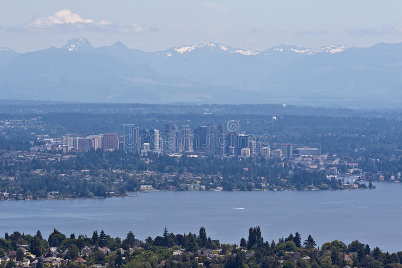 Bellevue and Seattle. The modern glass buildings of Bellevue, lake Washington, Seattle in the first plane and the mountains with snow peaks in the horizon royalty free stock images