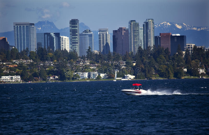 Bellevue WA Skyline Lake Washington. City of Bellevue from Lake Washington with Speed Boat and Snow Capped Mountains in Background royalty free stock image
