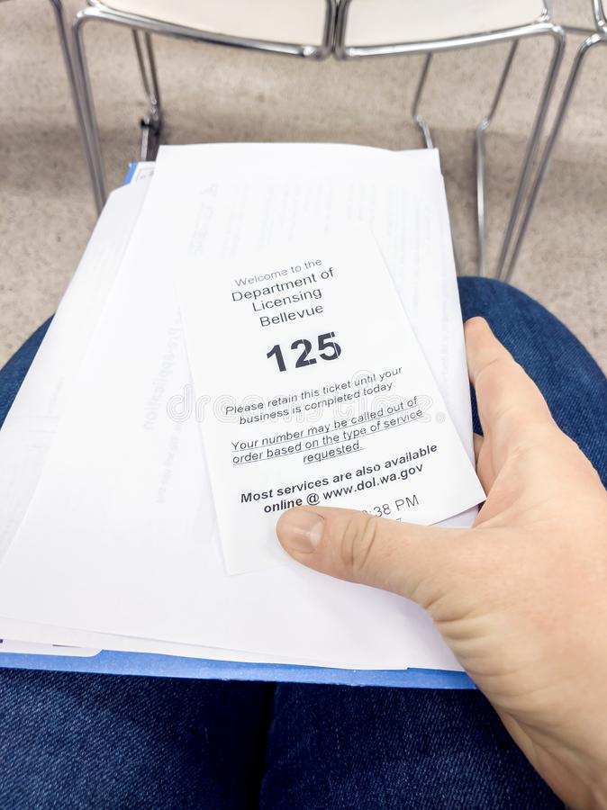 Person holding their waiting number ticket and license documents in the waiting area of stock photos