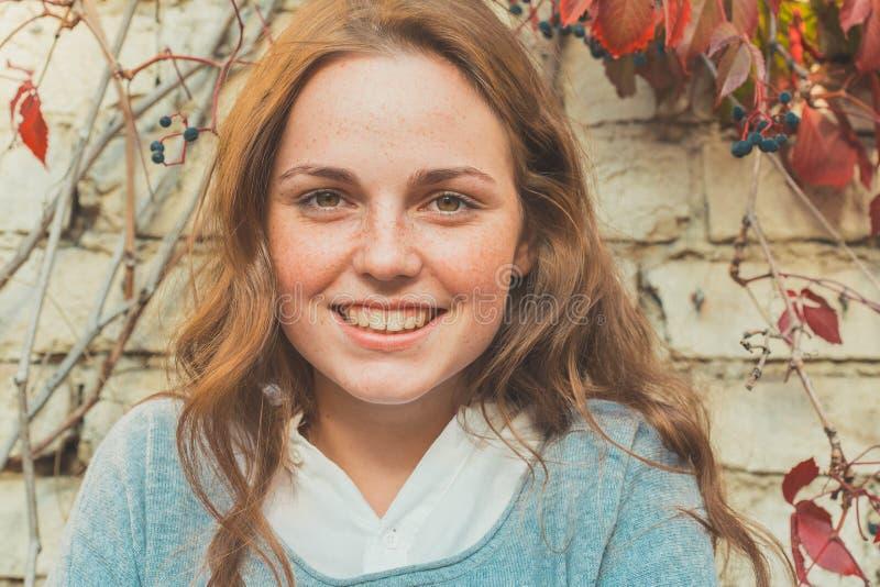 Belleza al aire libre Retrato sonriente de la mujer joven y feliz con las pecas Fondo de la pared de ladrillo con las flores fotos de archivo libres de regalías