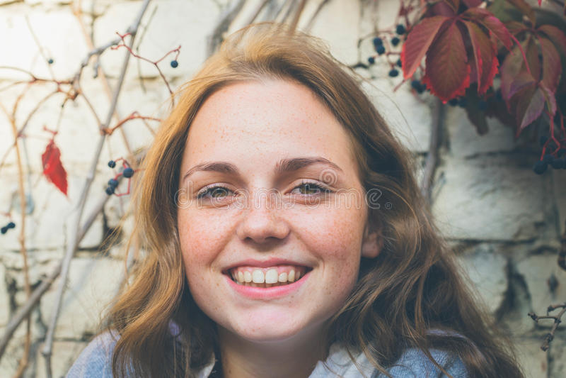 Belleza al aire libre Retrato sonriente de la mujer joven y feliz con las pecas Fondo de la pared de ladrillo con las flores foto de archivo