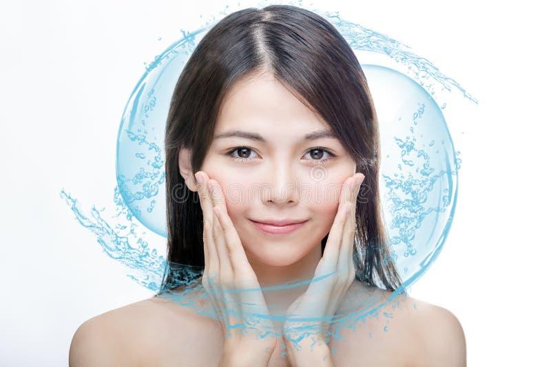 Belleza asiática con el chapoteo del agua azul imagenes de archivo