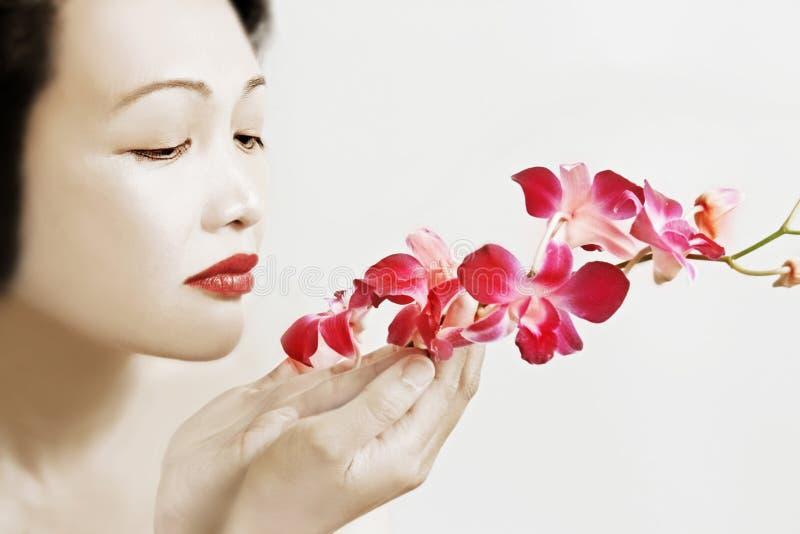 Belleza asiática con las orquídeas fotos de archivo
