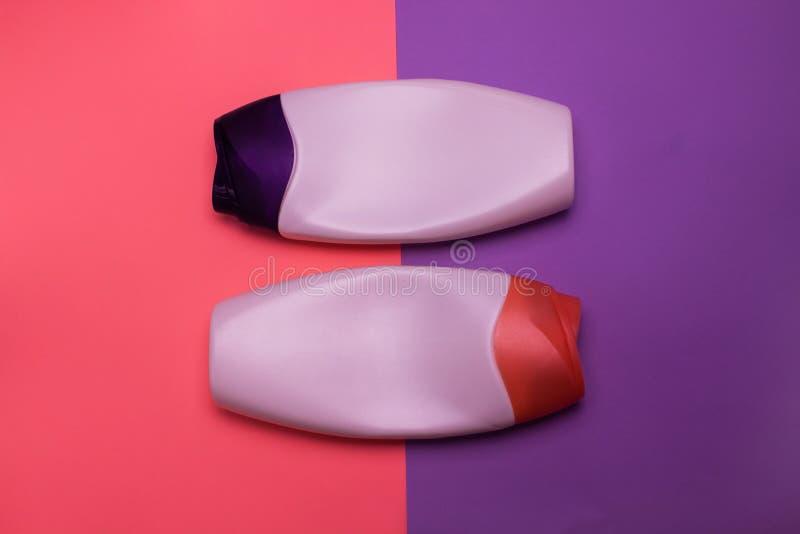 Belleza, botellas decorativas de los cosm?ticos Rosa y fondo p?rpura de los colores, endecha plana, visi?n superior, estilo minim imagen de archivo