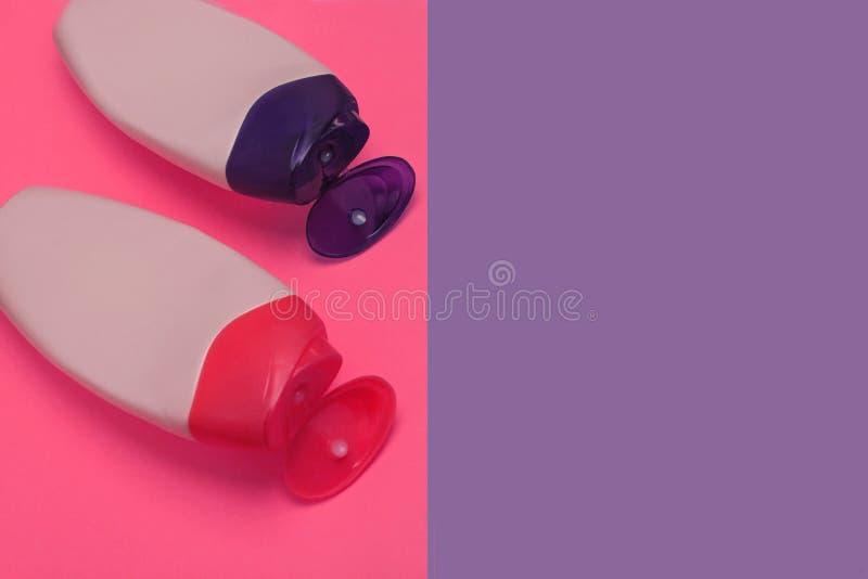 Belleza, botellas decorativas de los cosm?ticos Rosa y fondo p?rpura de los colores, endecha plana, visi?n superior, estilo minim imagenes de archivo