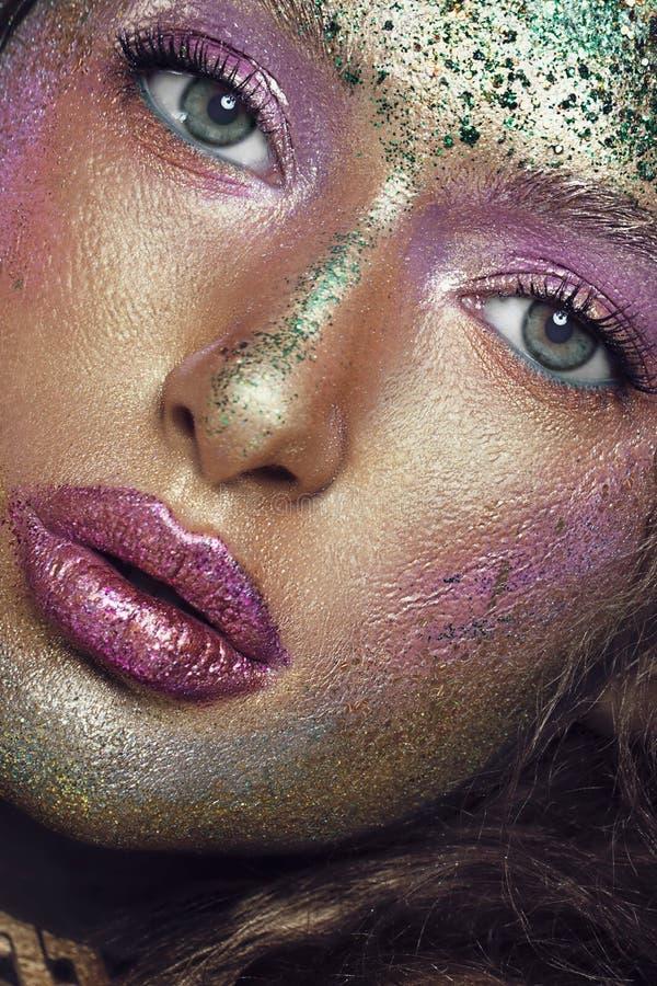 Belleza, cosm?ticos y maquillaje Los ojos m?gicos miran con creativo brillante componen Tiro macro de la cara de la mujer hermosa foto de archivo