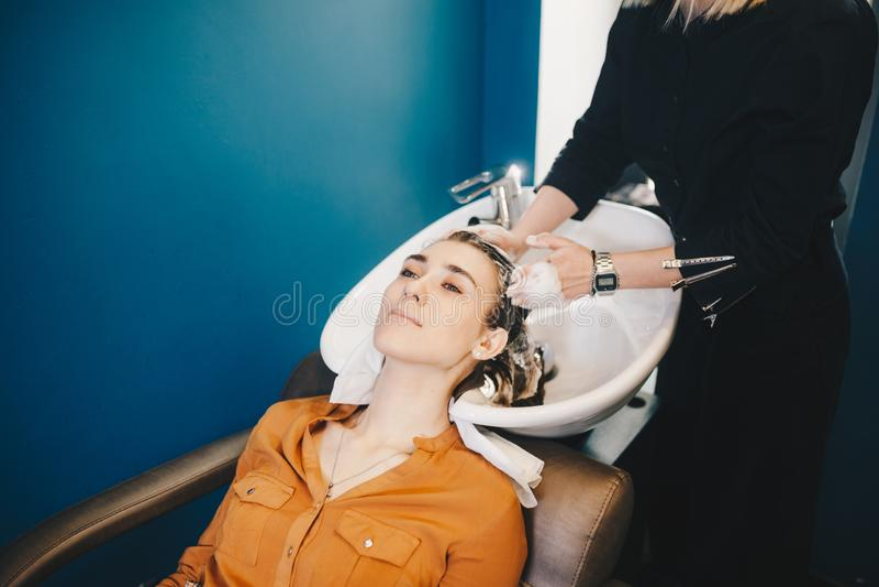 Belleza, cuidado del cabello y concepto de la gente - mujer joven feliz con la cabeza del lavado del peluquero en la peluquer?a imagen de archivo