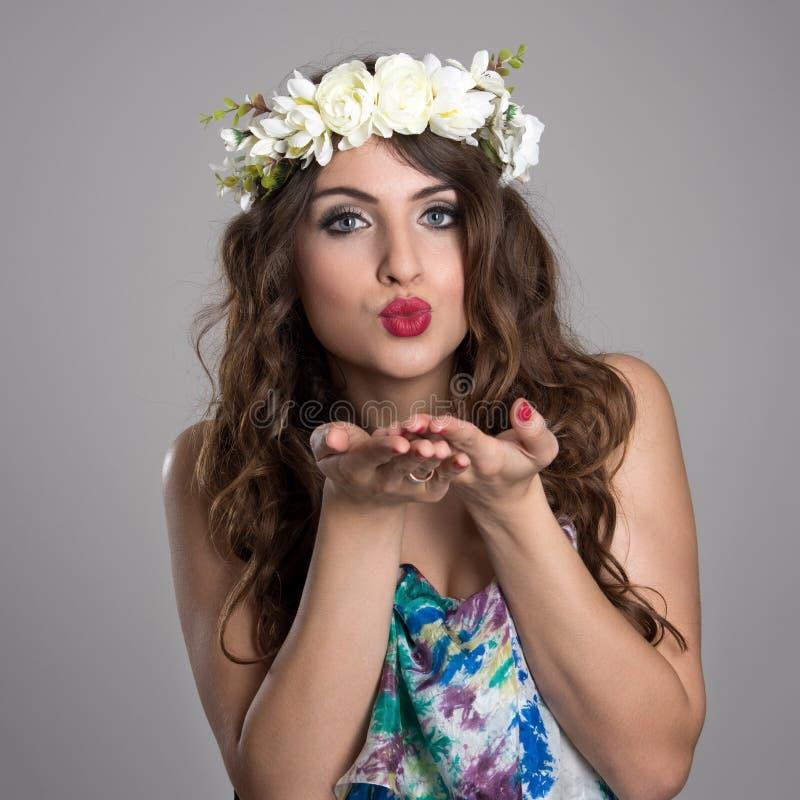 Belleza de hadas de la fantasía con beso que sopla de la guirnalda de las flores en la cámara fotos de archivo libres de regalías