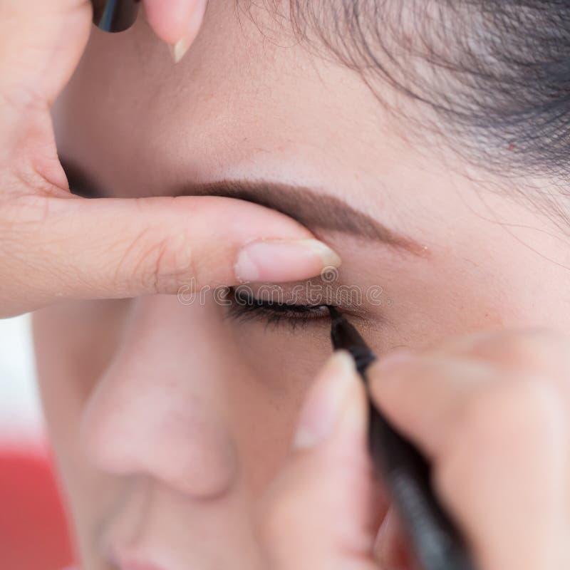 Belleza del maquillaje con el trazador de líneas del ojo del cepillo imagenes de archivo