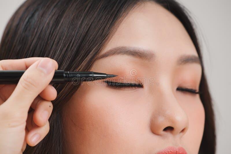 Belleza del maquillaje con el trazador de líneas del ojo del cepillo en cara bonita de la mujer imágenes de archivo libres de regalías
