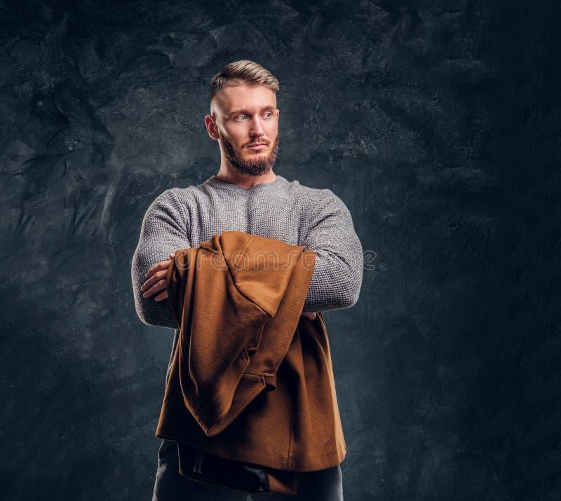 Belleza del ` s de los hombres, moda estacional Retrato de un varón elegante que sostiene capa de la demi-estación Foto del estud foto de archivo