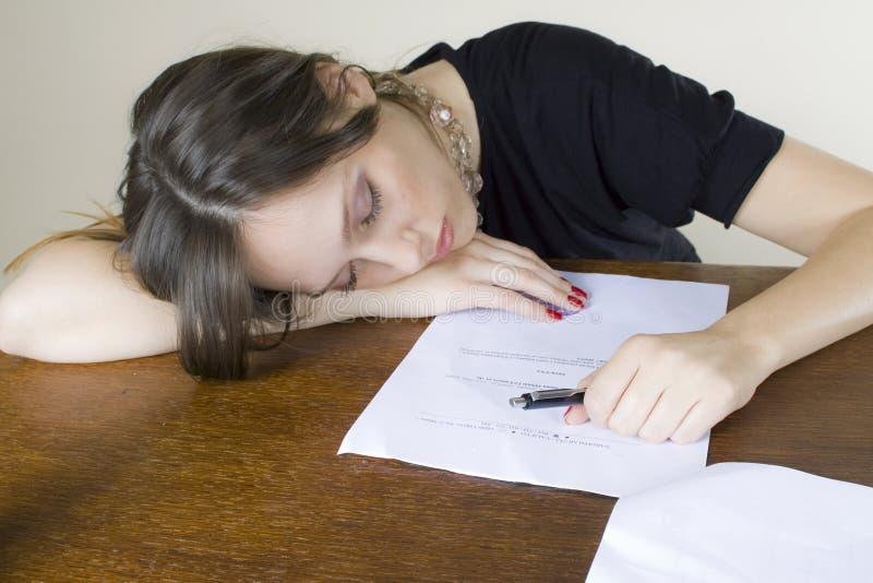 Secretaria atractiva de la muchacha dormida en su mesa fotos de archivo