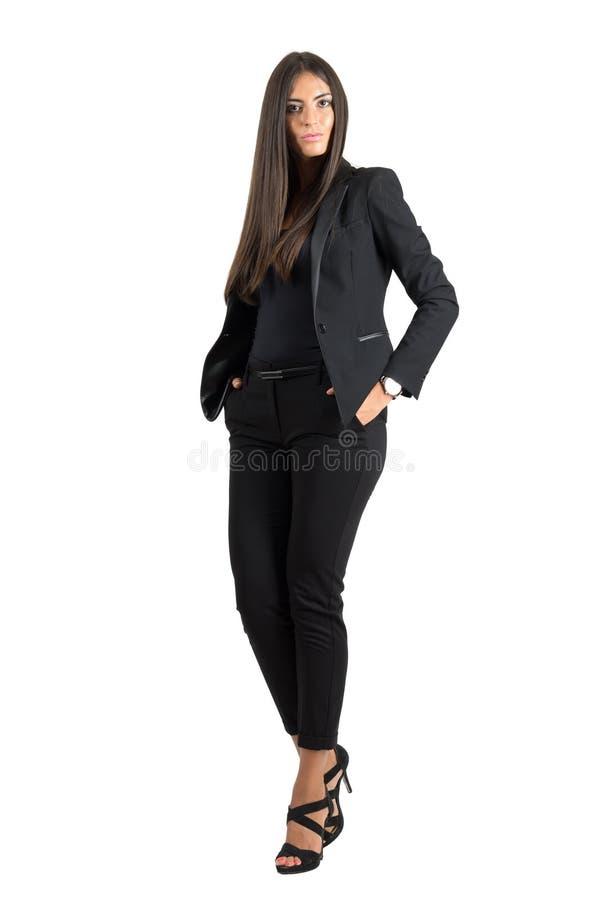 Belleza elegante seria del negocio en traje negro con las manos en bolsillos foto de archivo libre de regalías