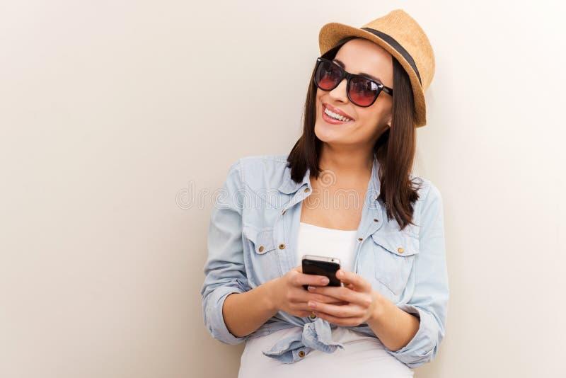 Belleza enrrollada con el teléfono móvil imagen de archivo