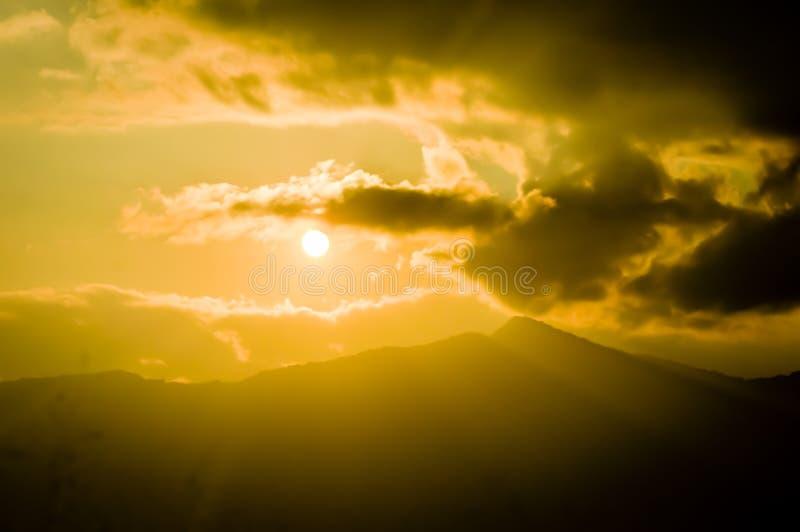 Belleza escénica del panorama magnífico de la puesta del sol con las nubes coloridas en el cielo anaranjado Fondo divino del ciel fotografía de archivo