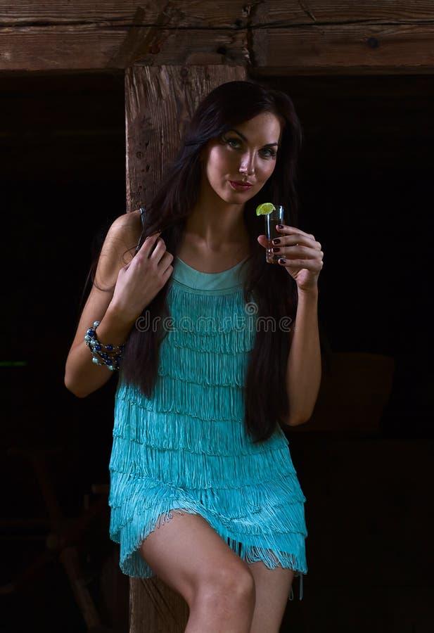 Belleza joven con tequila en la casa de madera vieja foto de archivo